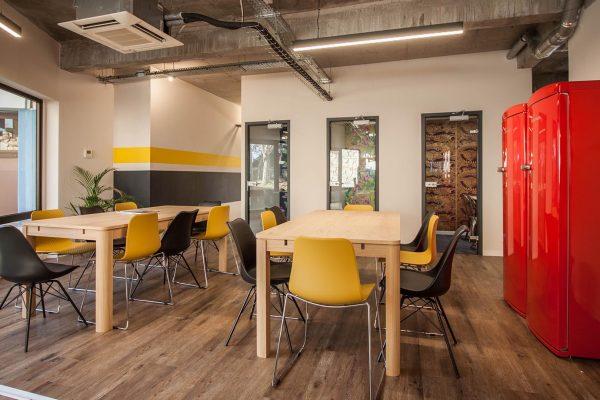 Un espace de travail à Sophia Antipolis avec des tables en open space et des cabines téléphoniques pour passer vos appels